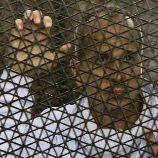 Al Jazeera journalist Peter Greste stands inside the defendants' cage in a Cairo courtroom in March (AP)