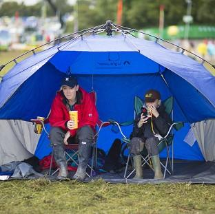 Festivalgoers Christina Birch and Ben, aged 8, from St Albans prepare for more wet weather at the Glastonbury Festival