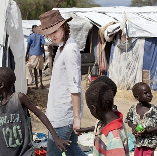 Keira Knightley holds hands with displaced children in Bor Camp, South Sudan