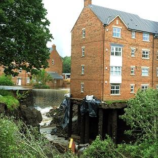 Water cascades past houses in Newburn after floods in 2012