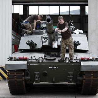 Trooper Tony Gibbs, of Yeovil (right), paints the barrel of a Challenger 2 tank alongside Trooper Scott Smith from Nottingham