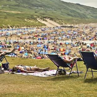 People relax in sunny weather at Woolacombe, North Devon, as the hot weat