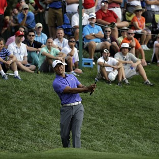 Tiger Woods, pictured, teed off at 8:35am local time alongside Phil Mickelson and Padraig Harrington (AP)