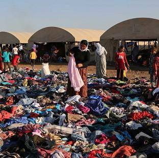 Displaced Iraqis from the Yazidi community look for clothes to wear among items provided by a charity organisation at the Nowruz camp in Derike, Syria (AP)