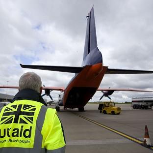 Staff from UK Aid watch as cargo is loaded on to an Antonov An-12B aircraft at East Midlands Airport as part of the UK Government's humanitarian response to the crisis in Iraq