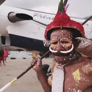 A member of the Moni Tribe poses by the aeroplane in Channel 4's Worst Place To Be A Pilot