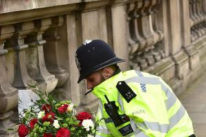 A police officer places flowers and a photo of Pc Keith Palmer on Whitehall near the Houses of Parliament in London, after seven people were arrested in raids in London, Birmingham and elsewhere linked to the Westminster terror attack. PRESS ASSOCIATION P