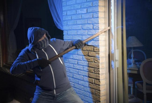 A burglar is opening the backdoor of a house thief STOCK..