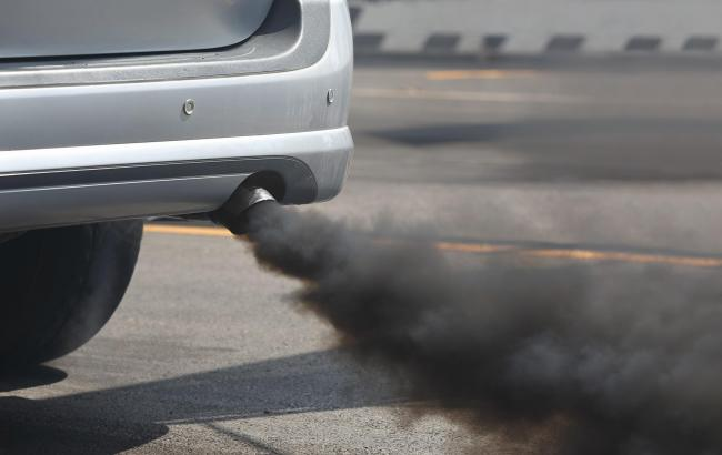 Air pollution from vehicle exhaust pipe on road..