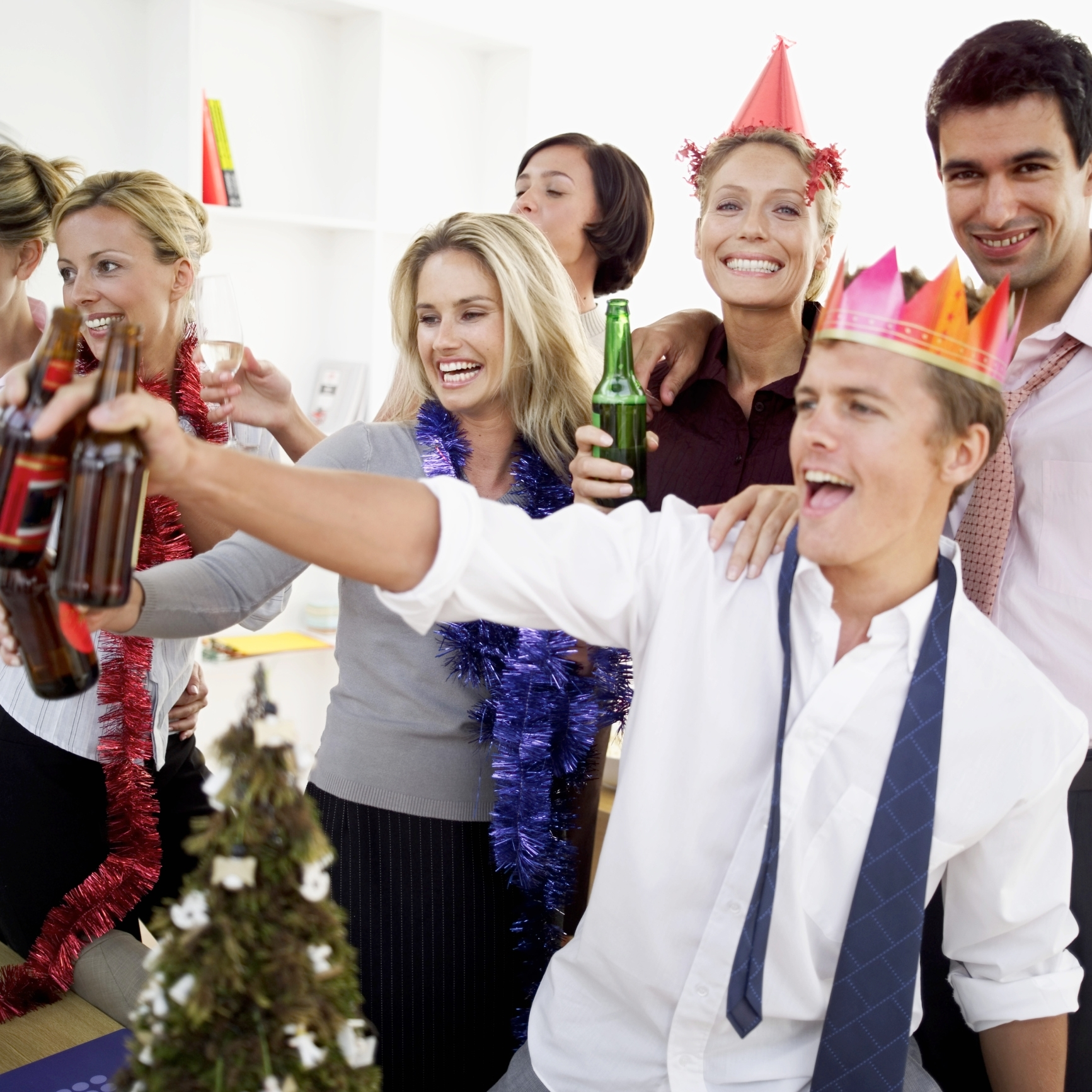 close-up of co-workers celebrating with beers at a office party.