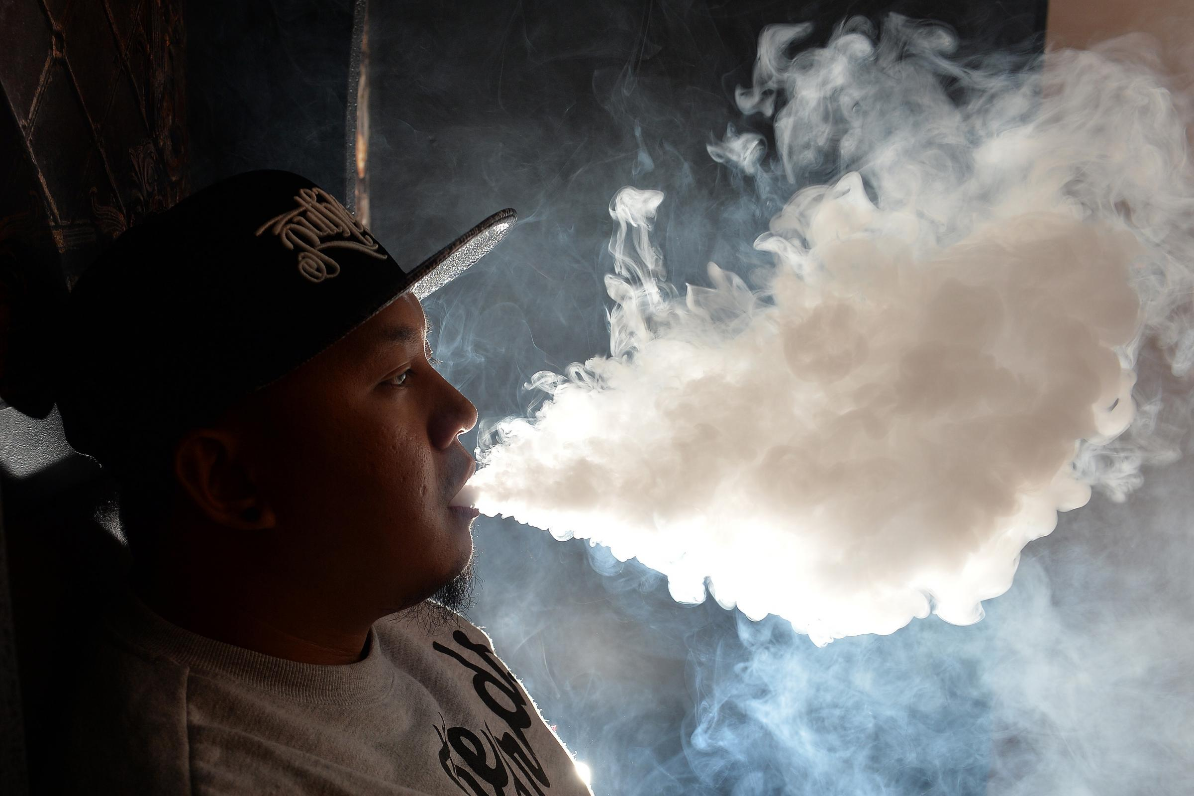 Puffing out smoke from an e-cigarette. New research suggests vaping may increase the risk of cancers. (John Stillwell/PA)