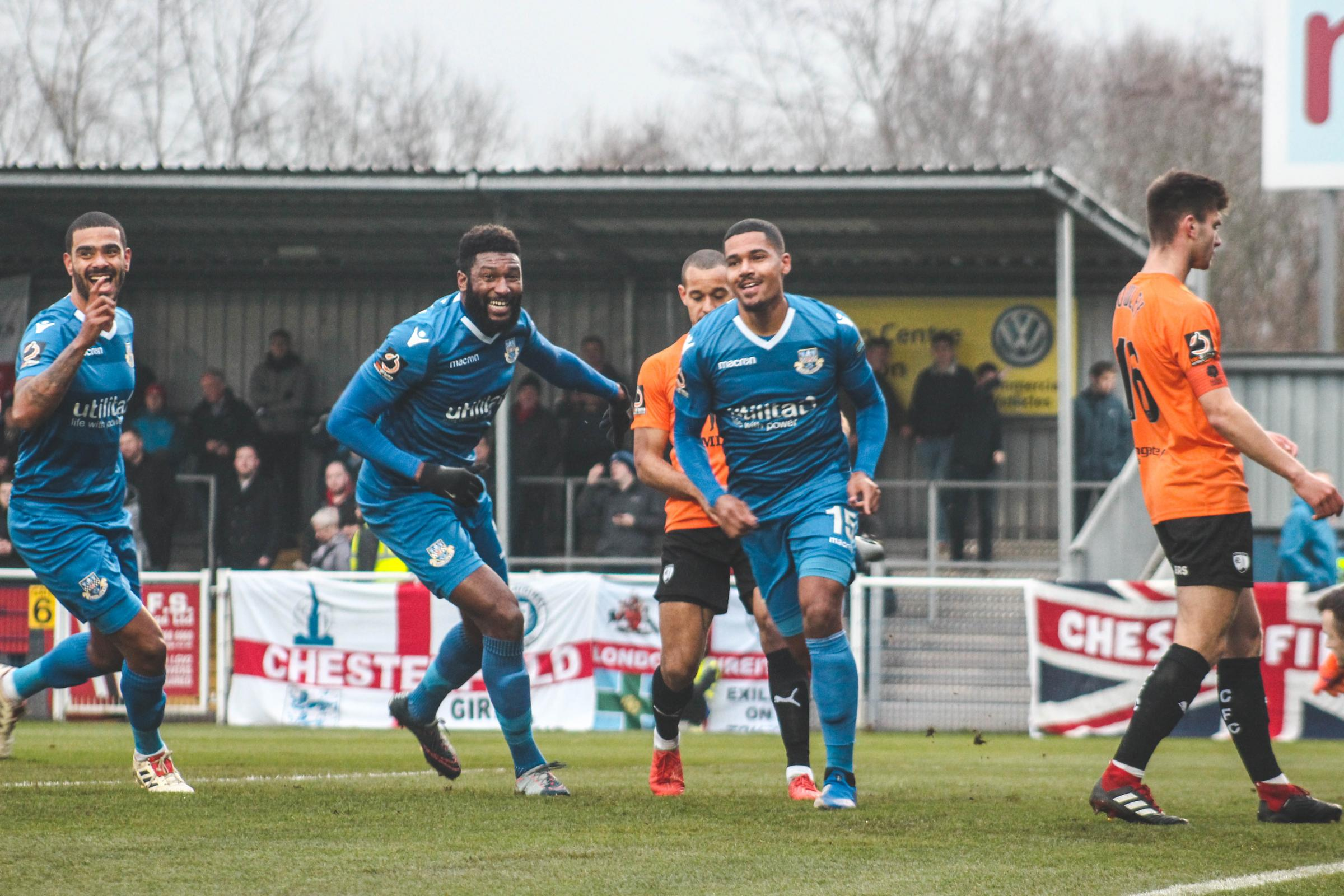 Alex Wynter (right, blue) runs away after scoring. Photo: Tom Mulholland.